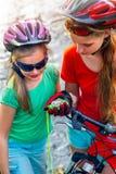 Las bicis que completan un ciclo el casco que lleva de la muchacha de los niños miran el compás Imágenes de archivo libres de regalías