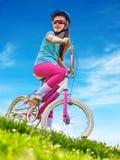 Las bicis que completan un ciclo el casco que lleva de la muchacha montan la bicicleta Imagen de archivo libre de regalías