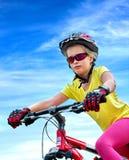 Las bicis que completan un ciclo el casco que lleva de la muchacha montan la bicicleta Imágenes de archivo libres de regalías