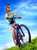 Las bicis que completan un ciclo el casco que lleva de la muchacha montan la bicicleta contra el cielo azul Imagenes de archivo