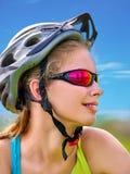 Las bicis que completan un ciclo el casco que lleva de la muchacha montan la bicicleta contra el cielo azul Fotografía de archivo