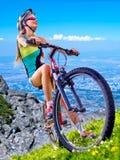 Las bicis que completan un ciclo el casco que lleva de la muchacha montan la bicicleta contra el cielo azul Imagen de archivo libre de regalías