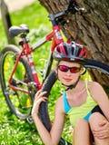 Las bicis que completan un ciclo el casco que lleva de la muchacha tienen resto que se sienta debajo de árbol Fotografía de archivo