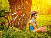 Las bicis que completan un ciclo el casco que lleva de la muchacha tienen resto que se sienta debajo de árbol Imágenes de archivo libres de regalías