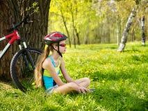 Las bicis que completan un ciclo el casco que lleva de la muchacha tienen un resto que se sienta debajo de árbol Fotos de archivo libres de regalías