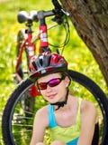 Las bicis que completan un ciclo el casco que lleva de la muchacha tienen un resto que se sienta debajo de árbol Imagen de archivo