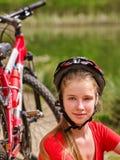 Las bicis que completan un ciclo el casco que lleva de la muchacha tienen un resto que se sienta debajo de árbol Fotos de archivo