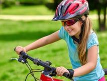 Las bicis que completan un ciclo a la muchacha montan la bicicleta en hierba verde en el parque al aire libre Fotografía de archivo libre de regalías