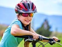 Las bicis que completan un ciclo a la muchacha montan la bicicleta en hierba verde en el parque al aire libre Fotografía de archivo