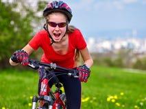 Las bicis que completan un ciclo a la muchacha montan la ciudad de la bicicleta hacia fuera Imagenes de archivo