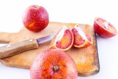 Las bio naranjas sangrientas cortaron por la mitad en una placa Fotografía de archivo