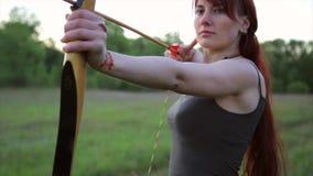 Las blancos femeninas del tiroteo del arquero del pelo del jengibre con su arco y flecha con uno mismo hicieron tatoo de la alheñ almacen de metraje de vídeo