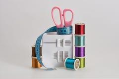 Las bobinas con color roscan, las agujas de costura, tijeras Fotos de archivo libres de regalías
