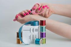 Las bobinas con color roscan, las agujas de costura, tijeras Foto de archivo