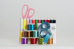 Las bobinas con color roscan, las agujas de costura, tijeras Fotos de archivo