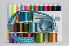Las bobinas con color roscan, las agujas de costura, tijeras Fotografía de archivo libre de regalías