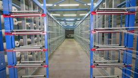 Las bobinas de la fibra giran en los estantes en una instalación grande almacen de video