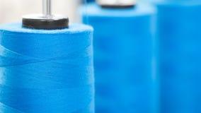 Las bobinas del primer con el azul coloreado roscan para las máquinas de materia textil industriales, fondo texturizado azul de l Fotos de archivo libres de regalías