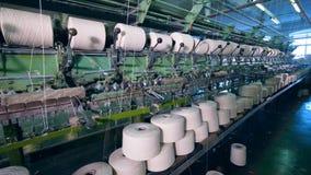 Las bobinas grandes giran, encanillando los hilos en las máquinas de la fábrica almacen de video