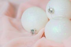Las bolas blancas del Año Nuevo y de la Navidad en un rosa Fotografía de archivo