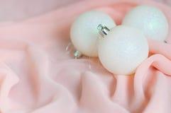 Las bolas blancas del Año Nuevo y de la Navidad en un rosa Imágenes de archivo libres de regalías