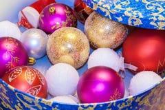 Las bolas coloreadas los juguetes de la Navidad están mintiendo en caja redonda azul con de Op. Sys. Imagen de archivo