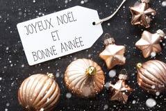 Las bolas de bronce de la Navidad, copos de nieve, Bonne Annee significan Feliz Año Nuevo Imagenes de archivo