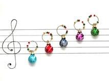 Las bolas de la decoración de la Navidad se arreglan en un trozo de papel como notas de la música Imagenes de archivo