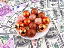 Las bolas de la Navidad fijaron en la placa blanca, fondo del dólar Foto de archivo libre de regalías