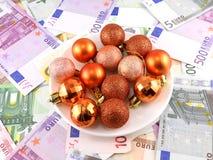 Las bolas de la Navidad fijaron en la placa blanca, fondo del dólar Imágenes de archivo libres de regalías