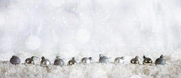 Las bolas de la Navidad reman en fondo nevoso del bokeh de la Navidad Imagen de archivo libre de regalías