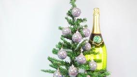 Las bolas del Año Nuevo en un árbol del Año Nuevo y una botella enorme de vino espumoso almacen de metraje de vídeo