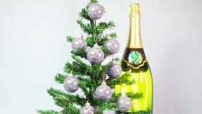 Las bolas del Año Nuevo en un árbol del Año Nuevo y una botella enorme de vino espumoso almacen de video