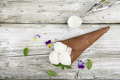 Las bolas del helado cremoso de vainilla en un chocolate curruscante asaltan con las flores de la viola y las hojas de menta come Imagen de archivo libre de regalías