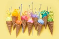 Las bolas del hilado mienten en un cono de la galleta para el helado Lanas coloreadas Foto de archivo libre de regalías