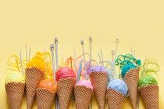 Las bolas del hilado mienten en un cono de la galleta para el helado Lanas coloreadas Foto de archivo