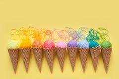 Las bolas del hilado mienten en un cono de la galleta para el helado Lanas coloreadas Imágenes de archivo libres de regalías