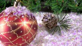 Las bolas del ` s del Año Nuevo mienten en nieve contra la perspectiva de un abeto de la Navidad almacen de video