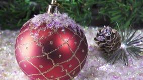 Las bolas del ` s del Año Nuevo mienten en nieve contra la perspectiva de un abeto de la Navidad metrajes
