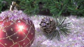 Las bolas del ` s del Año Nuevo mienten en nieve contra la perspectiva de un abeto de la Navidad almacen de metraje de vídeo