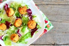 Las bolas fritas de oro de la patata con las semillas de calabaza sirvieron con la mezcla y la albahaca de la lechuga en una plac Foto de archivo libre de regalías