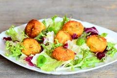 Las bolas fritas del puré de patata con las semillas de calabaza sirvieron con lechuga y albahaca frescas en una placa Fotos de archivo libres de regalías