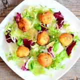Las bolas fritas del puré de patata con las semillas de calabaza sirvieron con lechuga y albahaca frescas en una placa y en fondo Fotos de archivo libres de regalías