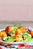 Las bolas fritas hechas en casa de la patata con las semillas de calabaza sirvieron con la mezcla y la albahaca de la lechuga en  Fotos de archivo