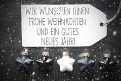 Las bolas negras de la Navidad, copos de nieve, Gutes Neues significan Feliz Año Nuevo Foto de archivo