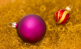 Las bolas púrpuras y rojas de la Navidad en el oro brillan Foto de archivo
