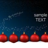 Las bolas rojas alinearon en parte inferior del blanco del â de la nieve Imagen de archivo libre de regalías
