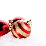 Las bolas rojas rayadas del Año Nuevo en nieve Imagen de archivo