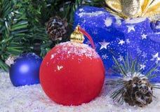 Las bolas rojas y azules del Año Nuevo en nieve y el regalo empaquetan Fotografía de archivo libre de regalías
