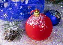 Las bolas rojas y azules del Año Nuevo en nieve y el regalo empaquetan Imagen de archivo libre de regalías